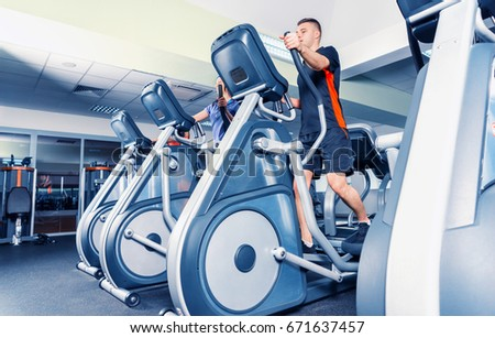 Bottom view on group of young people diligently exercising on the crosstrainer machines in fitness center #671637457