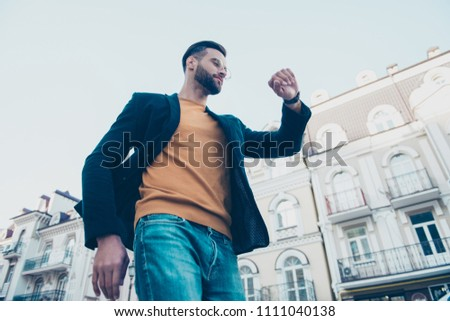 Bottom view portrait of attractive responsible man in jeans casual outfit looking at watch in wrist hurry up for meeting with partners #1111040138