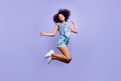Bottom view portrait of crazy positive girl in jeans outfit jumping in air enjoying daydream having weekend vacation holiday isolated on violent background. Luck success concept