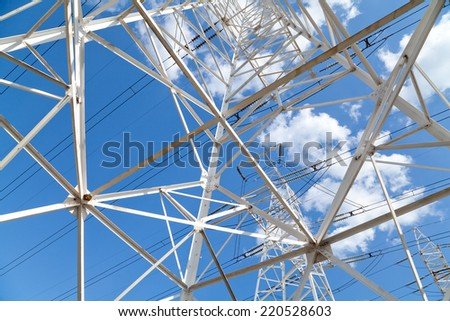 Bottom view power transmission high voltage lines on the white supports against blue sky