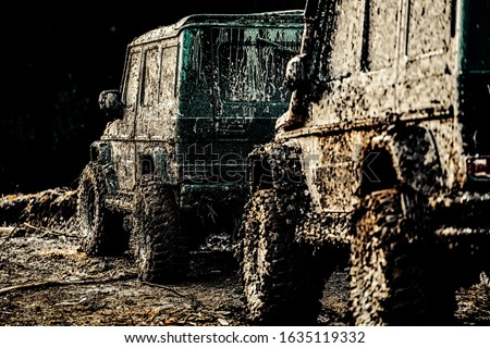 Photo of  Bottom view to big offroad car wheel on country road and mountains backdrop. Jeep outdoors adventures. Jeep crashed into a puddle and picked up a spray of dirt