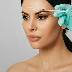 Botulinum toxin injections in a woman's forehead for blocking mimic wrinkles. Beautiful face with arrows, wrinkles removal concept