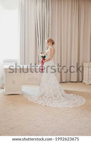 Boudoir morning of the bride in luxury interior. Pretty young Bride in elegant wedding dress with her bouquet. Blonde-haired woman with wedding hair-style in royal room of hotel. Wedding day ceremony