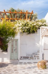Bougainvillea flowers around the house with a balcony and flowers. Mykonos.
