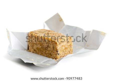 Bouillon cube in opened paper wrapping over white background