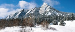 Boulder Colorado Flatirons frosted with blowing snow against a clear blue sky.