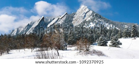Boulder Colorado Flatirons frosted with blowing snow against a clear blue sky. #1092370925