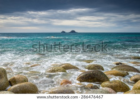Boulder covered beach at Porth Nanven at the end of Cot Valley with the Brisons on the Horizon, Cornwall England UK Europe