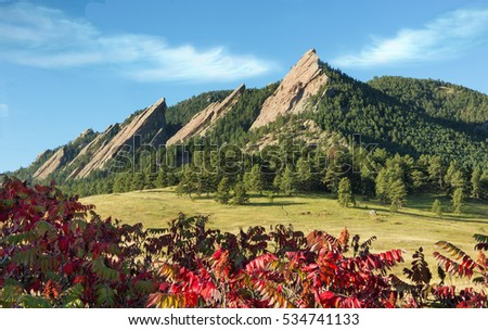 Boulder Flatirons. Red Sumac Fall Foliage in Foreground. Wispy Clouds Above Mountains.