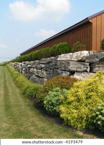 Boulder retaining wall at a commercial site with attractive plantings that include perennials, grasses and deciduous and evergreen shrubs