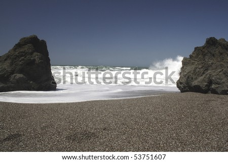 Boulders and footprints on California coast with waves rolling in onto a pebble beach with dark blue sky in the background.