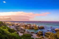 Boulders is a turqoise rocky and sheltered beach in cape town South Africa taken as sunset