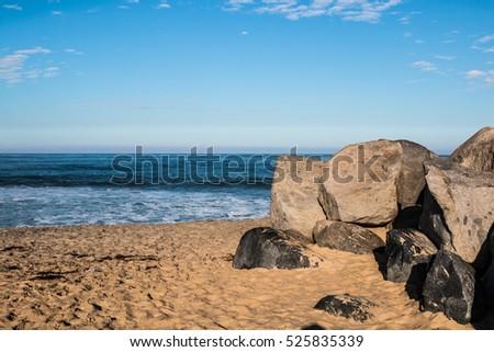 Boulders on sandy beach in Imperial Beach, California.