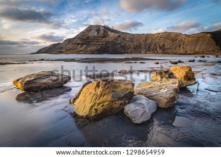 Boulders on the beach at Chapman's Pool, on the Jurassic Coast of Dorset, just catching the last of the evening light in winter