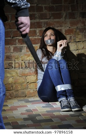 Bound girl sitting next to stone wall. Man with  knife approaching her.