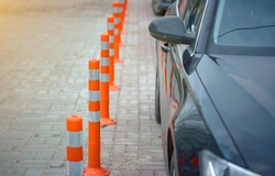 Boundary posts in the parking lot and pedestrian zone. Lot of striped orange reflictive traffic bollards placed in row for safety between pedestrian and parking zone. Public parking place in downtown
