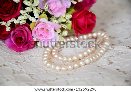 Bouquet and perls necklace on the lace.