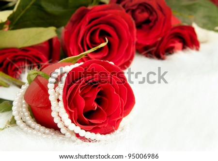 Bouquet beautiful red roses and pearl necklace; lay on white to fur