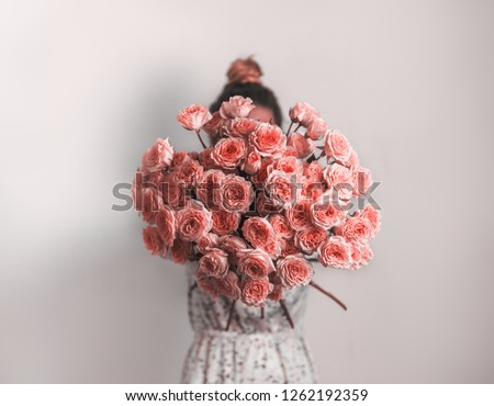 Bouquet in female hands. Bunch of Living Coral roses. Color of year 2019 Living Coral concept.