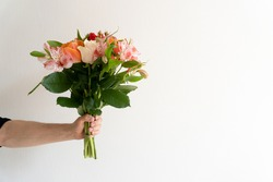 Bouquet of beautiful flowers in mans hand on white background. Minimalistic concept. Space for text.