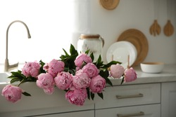 Bouquet of beautiful pink peonies in kitchen sink