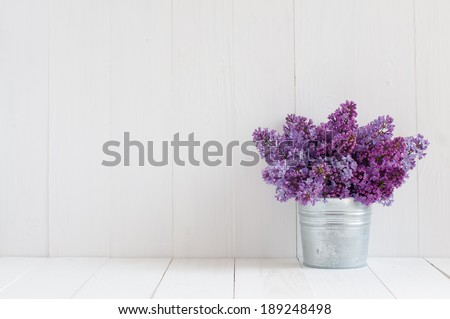 Bouquet of beautiful spring flowers of lilac in a vase on a white vintage wooden board, home decor in a rustic style