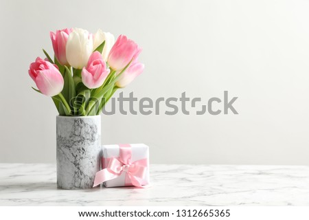 Bouquet of beautiful spring tulips in vase and gift box on marble table against light background. International Women's Day