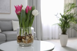 Bouquet of beautiful tulips with bulbs on table indoors. Space for text
