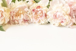 Bouquet of beige-pink peony flowers on a light paper background with space for text. Image for the design of greeting cards on the theme of wedding, Valentine's Day, declaration of love