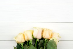 Bouquet of beige roses on white wooden vintage background, flat lay, top view, copy space. Mothers day. Valentines day.