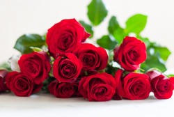 Bouquet of blossoming dark red roses lying on the table. Clear background. Valentine's Day love gift.