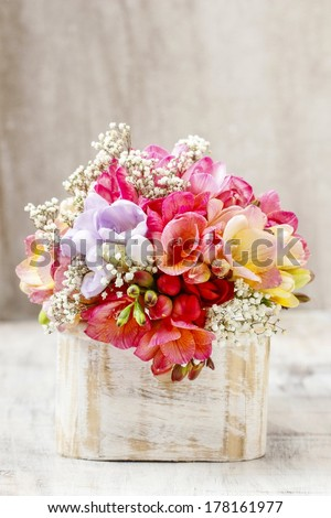 Bouquet of colorful freesia flowers in wooden shabby chic box. Copy space