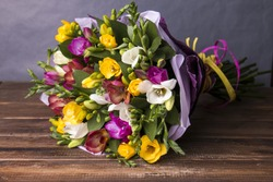 Bouquet of colorful fresh freesia on a wooden background
