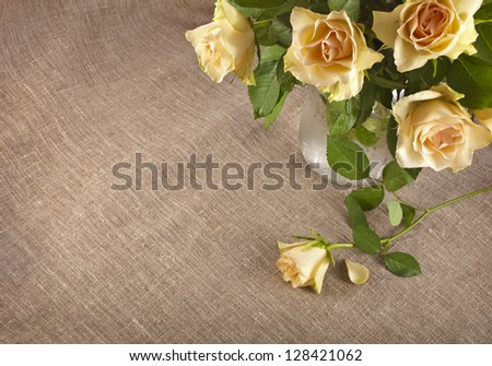 bouquet of cream tea roses on canvas cloth texture with copy space for text