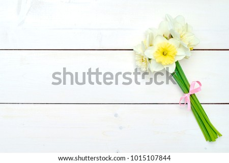 Bouquet of daffodil flowers on white wooden background, copy space. Top view, flat lay. White narcissus. Spring flowers. Greeting card for March 8 (Women's Day), Mother's day. Spring easter background