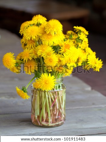 bouquet of dandelions on wooden table