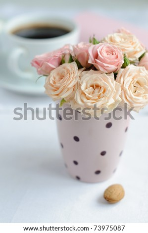 bouquet of delicate pink roses in a cup on the table