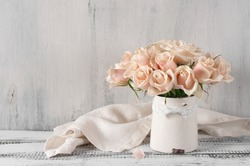 Bouquet of delicate pink roses in vintage tin vase on white rustic wooden background. Shabby chic home decor.