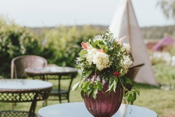 Bouquet of different flowers in a vase on the table, preparing for the event