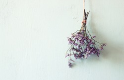 bouquet of dried flowers hanging on rope against wooden background