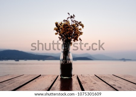 Stock Photo Bouquet of dried flowers in glass jar or bottle on wooden table over blurred sunset behind mountain and sea view background. Vase on table outdoor decoration with dramatic evening dawn scenic.