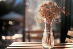 bouquet of dried flowers on a table of a street cafe, on a summer sunny day
