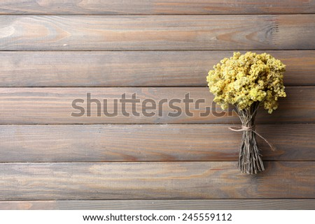 Bouquet of dried flowers on wooden planks background