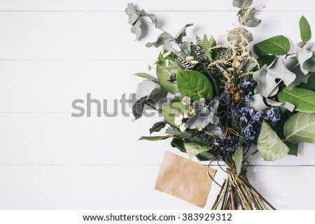 Stock Photo Bouquet of dried wild flowers on white table background  with natural wood vintage planks wooden texture top view horizontal, empty space for publicity information or advertising text
