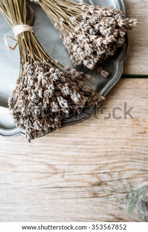 Bouquet of dry Lavender on a vintage silver plate and wooden background