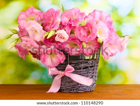 bouquet of eustoma flowers in  wicker vase, on wooden table, on green background