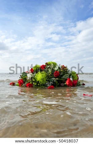 Bouquet of flowers, adrift in the sea, representing a watery grave