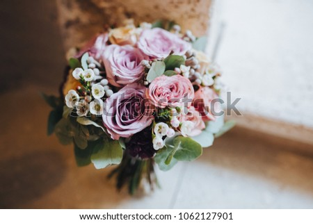 bouquet of flowers and greens stands on the stone steps of old house