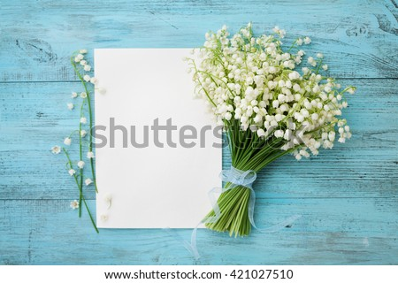 Bouquet of flowers lily of the valley and empty paper sheet on turquoise rustic table from above, beautiful vintage card, top view, copy space for text, flat lay