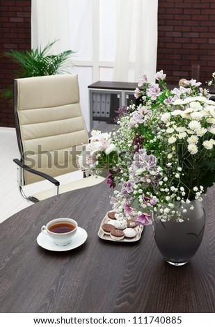 Bouquet Of Flowers On A Desk At Modern Office Stock Photo